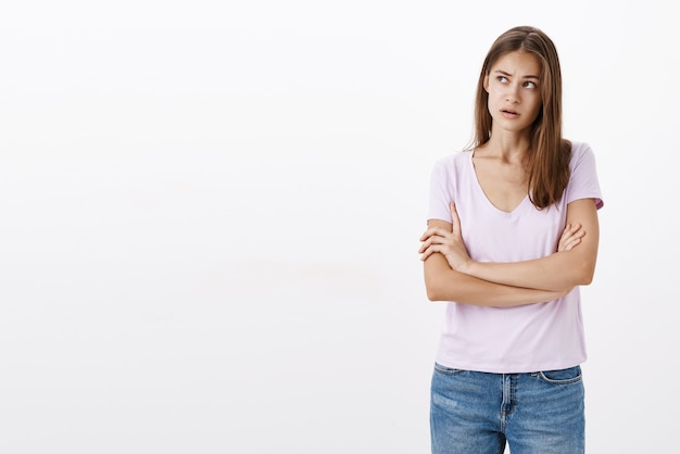 Konzentrierte ahnungslose, verwirrte, attraktive, stilvolle junge frau, die die hände auf der brust gekreuzt hält und die augenbrauen hochzieht und auf die obere linke ecke blickt, um sich an die situation zu erinnern