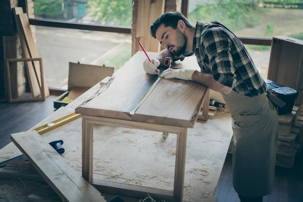 Konzentrierte arbeiter mann restaurieren holzplatte tisch verwenden bleistift lineal messen länge auf schreibtischoberfläche in haus garage