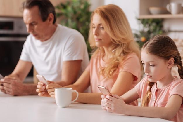 Konzentrierte besessene süchtige familie, die zu hause sitzt und sich entspannt, während sie elektronische geräte benutzt