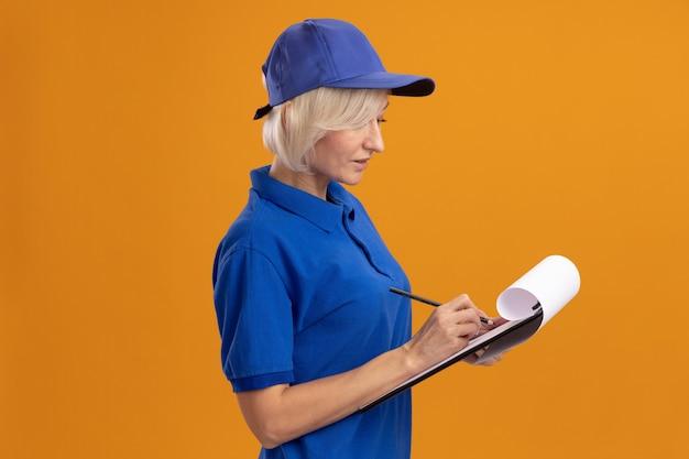 Konzentrierte blonde lieferfrau mittleren alters in blauer uniform und mütze, die in profilansicht steht und mit bleistift auf zwischenablage schreibt, isoliert auf oranger wand mit kopierraum