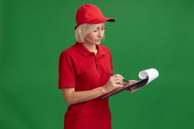 Konzentrierte blonde lieferfrau mittleren alters in roter uniform und mütze mit bleistift und zwischenablage in zwischenablage