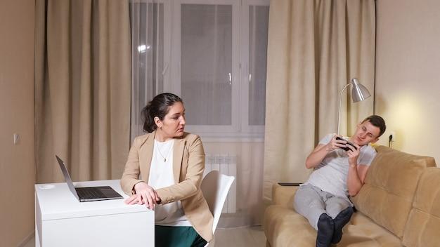 Konzentrierte brünette typen auf grauem laptop sitzen auf stuhl am tisch und ehemann, der auf dem sofa liegt und spiel spielt