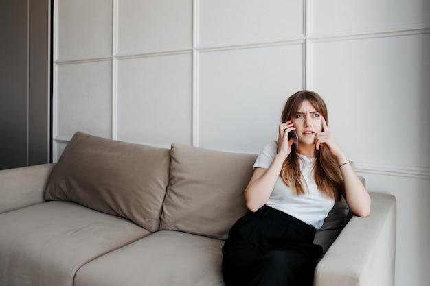 Konzentrierte ernsthafte frau, die zu hause am telefon sitzt und auf dem sofa sitzt