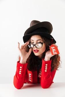 Konzentrierte ernsthafte junge kaukasische dame, die hüte durch verkauf trägt.