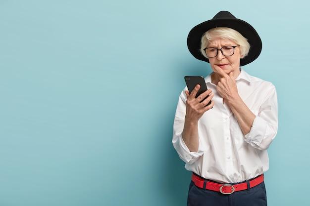 Konzentrierte ernsthafte oma trägt modische kopfbedeckungen, outfit, konzentriert auf smartphone, liest aufmerksam nachrichten online, modelle über blaue wand mit freiem platz, überprüft e-mail-box. moderner rentner
