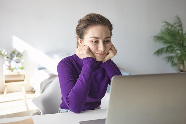 Konzentrierte ernsthafte studentin, die beim online-lernen, beim hören von vorträgen im internet oder beim lesen wissenschaftlicher artikel die hände unter den wangen hält