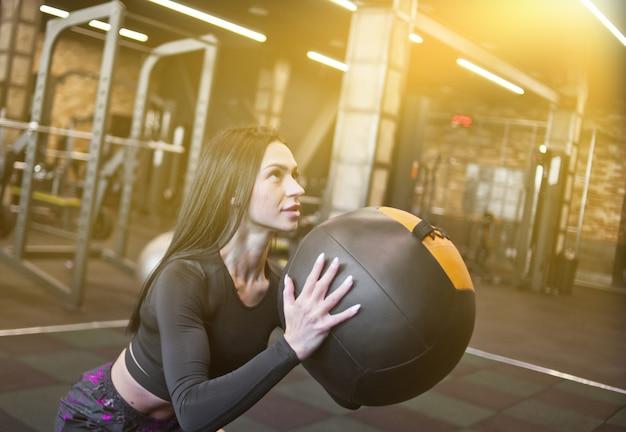 Konzentrierte fit frau in sportbekleidung, die übung mit med ball im fitnessstudio macht