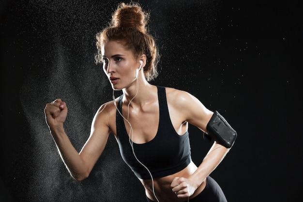 Konzentrierte fitnessfrau, die im studio läuft