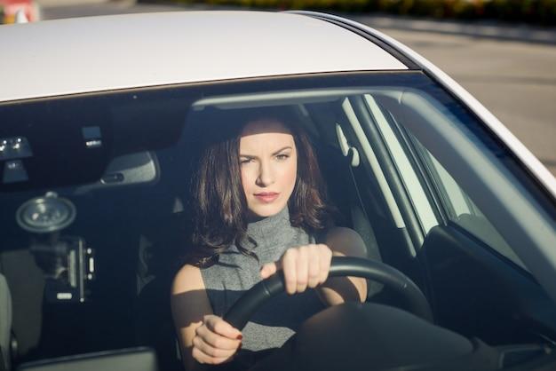 Konzentrierte frau, die ihr auto fahren