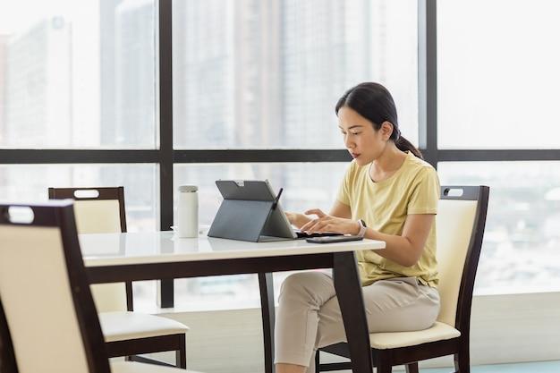 Konzentrierte frau, die im büro an ihrem tablet arbeitet