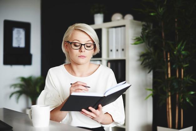 Konzentrierte frau, die in ihrem büro auf ein notizbuch schreibt
