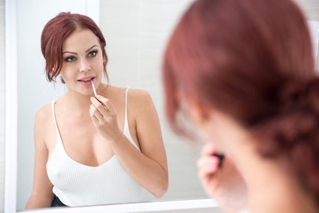 Konzentrierte frau, die lippenstift am spiegel anwendet
