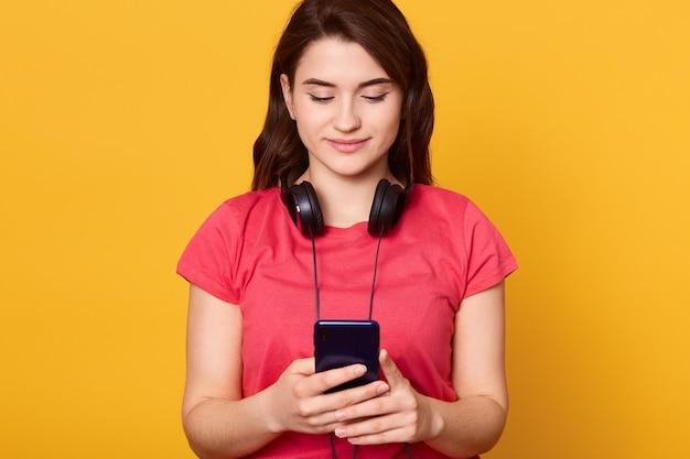 Konzentrierte frau mit dunklem haar hält smartphone in händen und schaut auf seinen bildschirm