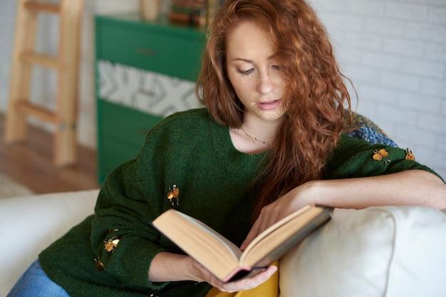 Konzentrierte frauen, die im wohnzimmer ein buch lesen