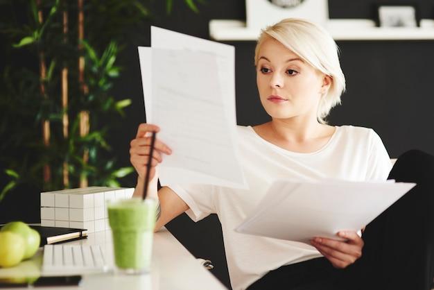 Konzentrierte geschäftsfrau, die dokumente im büro vergleicht