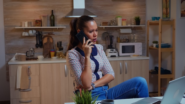 Konzentrierte geschäftsfrau während des telefonats spät in der nacht aus dem homeoffice. beschäftigter, fokussierter mitarbeiter, der moderne drahtlose netzwerktechnologie verwendet, überstunden für das lesen, schreiben, suchen
