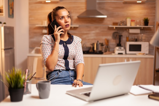 Konzentrierte geschäftsfrau während des telefonats spät in der nacht aus dem homeoffice. mitarbeiter, die um mitternacht moderne technologie verwenden, machen überstunden für job, geschäft, beschäftigt, karriere, netzwerk, lifestyle, drahtlos.