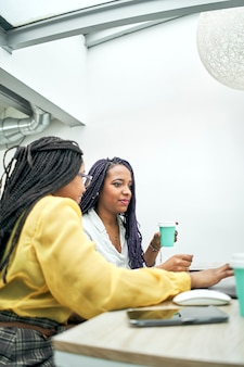 Konzentrierte geschäftsfrauen, die an einem schreibtisch in einem kreativen büro arbeiten und kaffee trinken