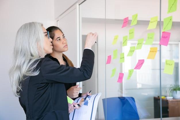 Konzentrierte geschäftsfrauen, die aufkleber auf glaswand betrachten. konzentrierte grauhaarige arbeitnehmerin, die sich notizen zur projektstrategie oder zum projektplan macht