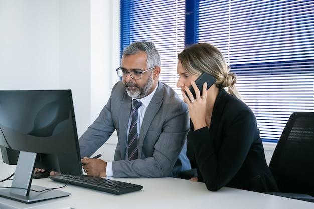 Konzentrierte geschäftskollegen, die zusammenarbeiten, am arbeitsplatz sitzen, auf dem handy sprechen und den computer benutzen. teamwork und kommunikationskonzept