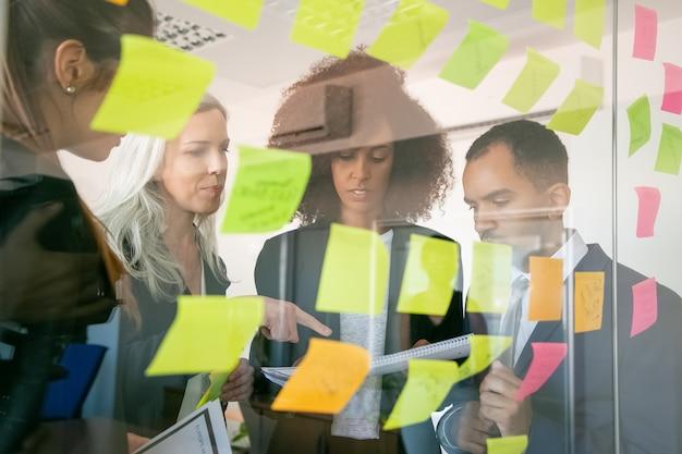 Konzentrierte geschäftsleute, die dokumente lesen und informationen prüfen. erfolgreiche konzentrierte arbeitgeber in anzügen treffen sich im büroraum und studieren berichte. teamwork-, geschäfts- und managementkonzept