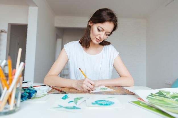Konzentrierte hübsche malerin, die am tisch im kunststudio sitzt und skizzen mit bleistift macht