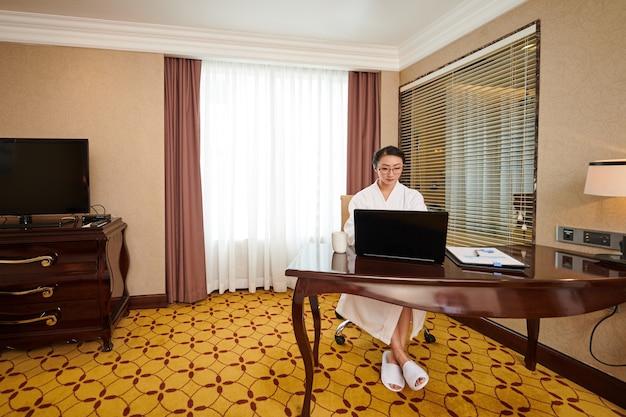 Konzentrierte junge asiatische geschäftsfrau im hotelbademantel, die während der urlaubsarbeit auf dem laptop tippt