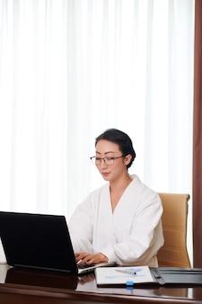 Konzentrierte junge asiatische geschäftsfrau in bademantel und brille, die am tisch sitzt und auf dem schoß tippt...