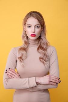 Konzentrierte junge blonde dame mit hellen make-up-lippen