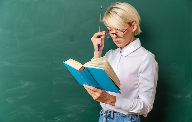 Konzentrierte junge blonde lehrerin, die eine brille im klassenzimmer trägt, die in der profilansicht vor der tafel steht, die einen zeigerstock hält und eine brille mit kopienraum liest