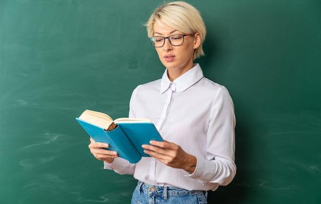Konzentrierte junge blonde lehrerin mit brille im klassenzimmer, die vor der tafel steht und ein buch hält und liest