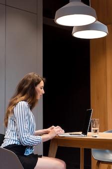 Konzentrierte junge dame in gestreiftem hemd und schwarzem rock, die an einem drahtlosen laptop arbeitet, während sie in einem hellen büro sitzt