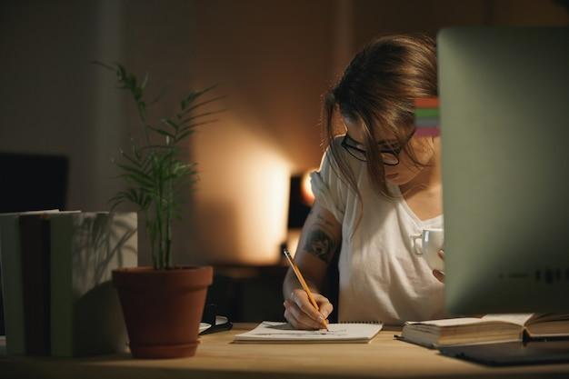 Konzentrierte junge frau designerin, die notizen mit computer schreibt