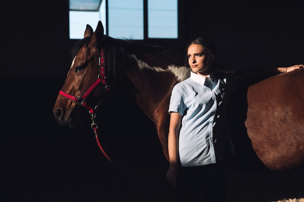 Konzentrierte junge frau, die draußen nahe ihrem pferd steht