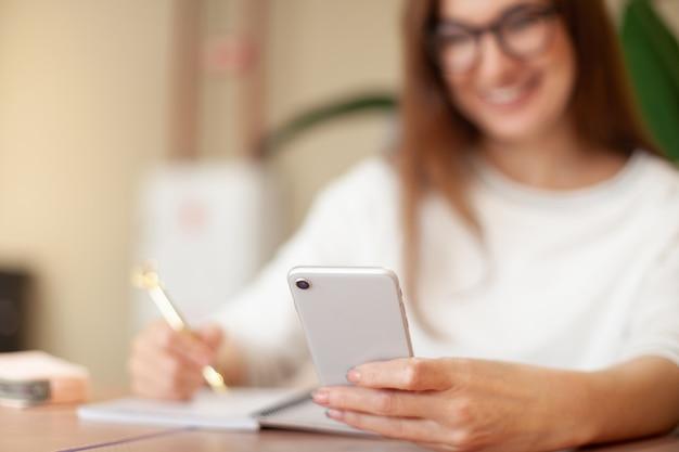 Konzentrierte junge frau, die eine aufgabenliste im notizblock schreibt und die mobile anwendung für die aufgabenverwaltung verwendet