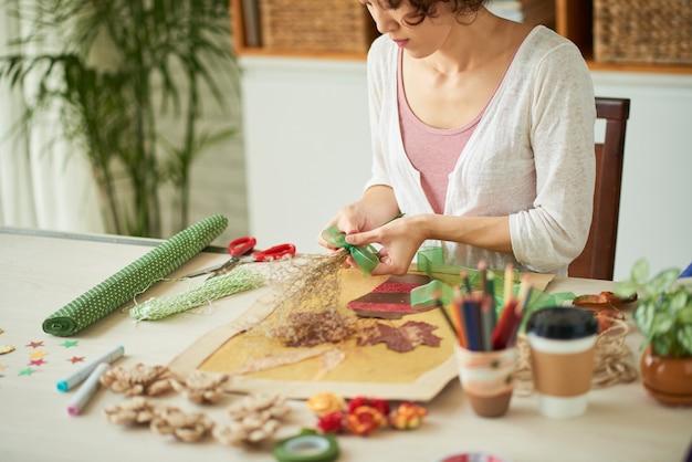Konzentrierte junge frau, die mit trockenblumen und anderen botanischen materialien arbeitet, um ganz...