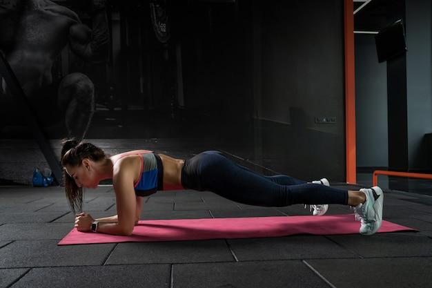 Konzentrierte junge frau, die plankenhaltung auf den ellbogen im fitnessstudio hält
