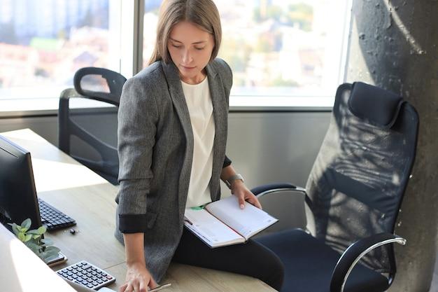 Konzentrierte junge frau, die während der arbeit im büro etwas aufschreibt.