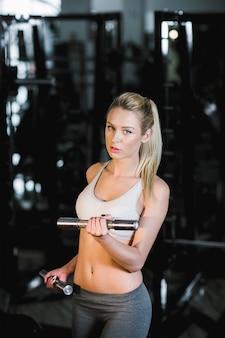 Konzentrierte junge frau, gewichte zu heben