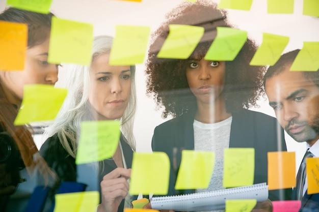Konzentrierte junge geschäftsleute, die auf aufkleber schauen und sich notizen machen. erfolgreiche konzentrierte kollegen in anzügen treffen sich im büroraum. teamwork-, business- und brainstorming-konzept