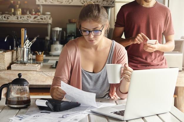 Konzentrierte junge kaukasische frau, die morgenkaffee beim arbeiten durch finanzen in der küche hat