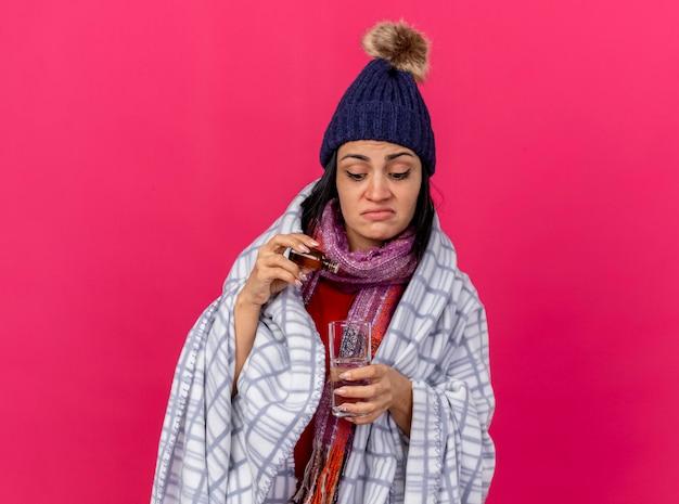 Konzentrierte junge kranke frau, die wintermütze und schal trägt, die in plaid eingewickelt sind, das medikament in glas wasser isoliert, isoliert auf rosa wand mit kopienraum