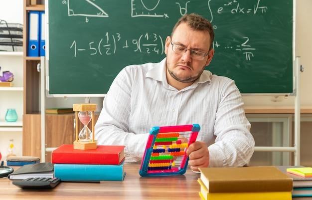 Konzentrierte junge lehrerin mit brille sitzt am schreibtisch mit schulmaterial im klassenzimmer mit abakus