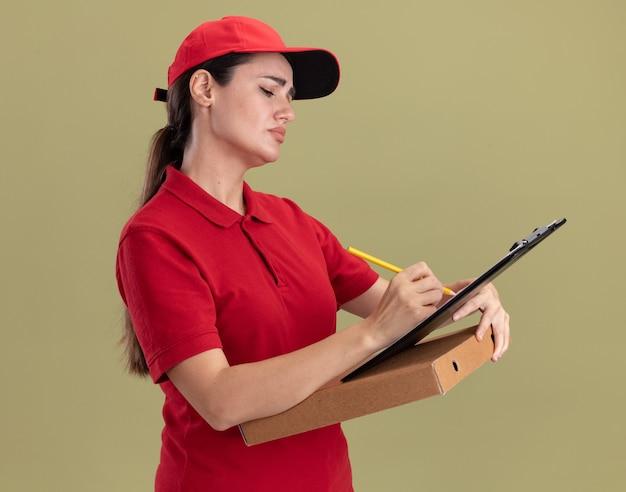Konzentrierte junge lieferfrau in uniform und mütze