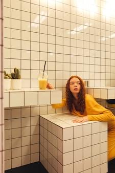 Konzentrierte junge rothaarige lockige dame, die im café sitzt
