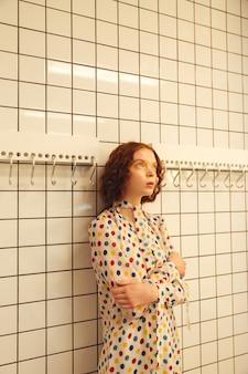 Konzentrierte junge rothaarige lockige dame, die im café steht