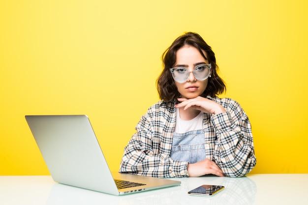 Konzentrierte junge schöne frau, die am laptop arbeitet