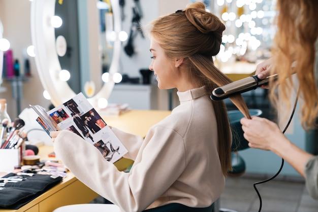 Konzentrierte junge schöne frau, die zeitschrift mit friseur im salon liest.