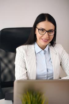 Konzentrierte junge schöne geschäftsfrau, die an laptop im hellen modernen büro arbeitet.