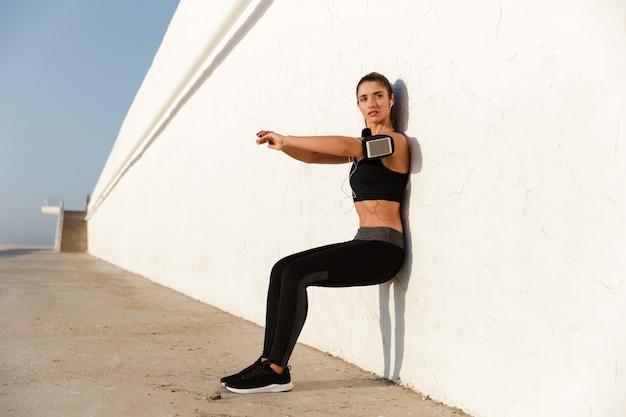 Konzentrierte junge sportfrau, die musik hört, macht sportübungen